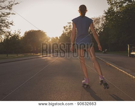 Young Woman Roller Skating In Park At Sunset