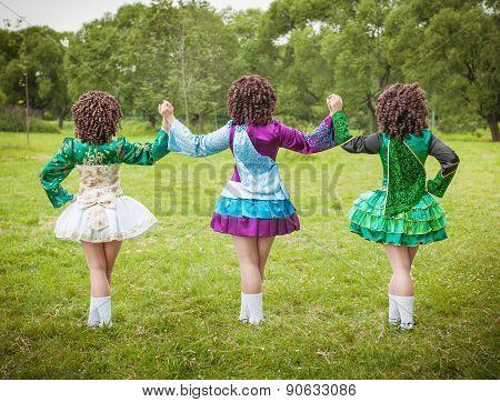 Three Girls In Irish Dance Dress And Wig Posing Outdoor
