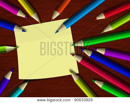 Colour Pencils Lying On Wooden Desk With Note