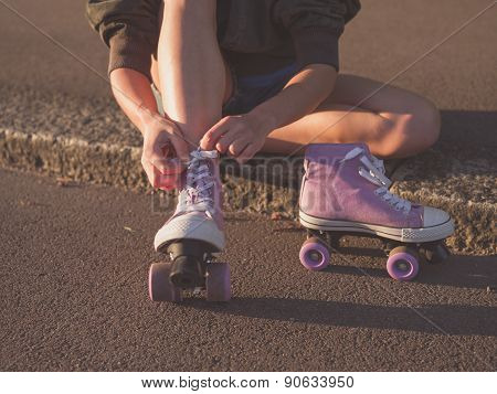 Woman Putting On Roller Skates In Park