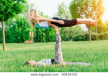 Couple Practicing Acroyoga In The Park