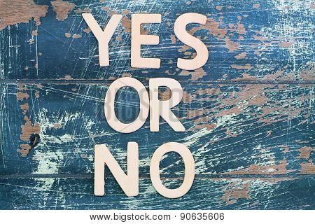Yes or no written with wooden letters on rustic wooden surface