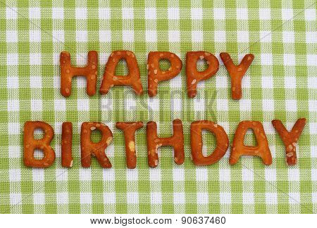 Happy birthday written with pretzel letters on checkered cloth