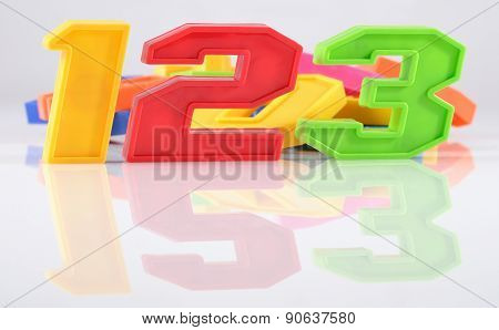 Colorful Plastic Numbers 123 With Reflection On White