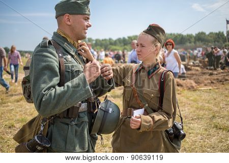 NELIDOVO, RUSSIA- JULY 12, 2014: Soviet soldier girl straightens uniform of a German soldier at the Battlefield 2014