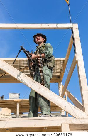 NELIDOVO, RUSSIA- JULY 12, 2014: Battlefield 2014: GI stands with the machine gun on observation tower