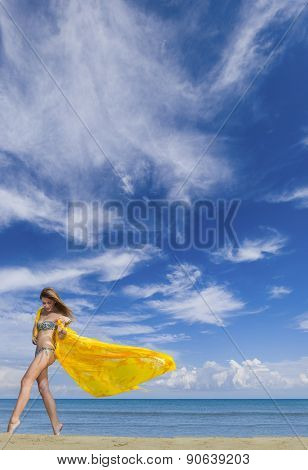 Young woman in bikini holding a yellow sarong on windy beach