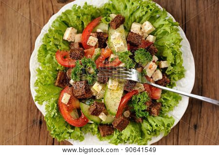 Vegetable Salad Made Of Lettuce, Cucumbers, Tomatoes, Cheese And Rye Toasts Top View