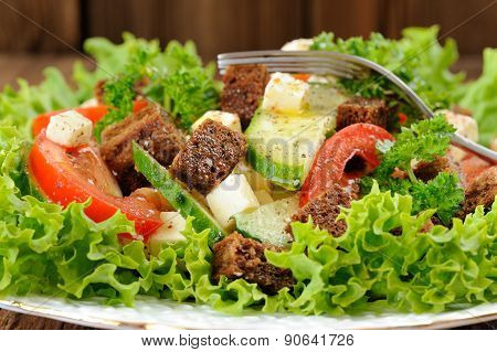Vegetable Salad Made Of Lettuce, Cucumbers, Tomatoes, Cheese And Rye Toasts With Fork Closeup