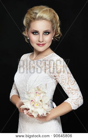 Young beautiful happy slim bride in lacy dress and bouquet of orchids