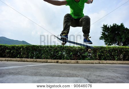 young woman skateboarder doing ollie trick at parking lot