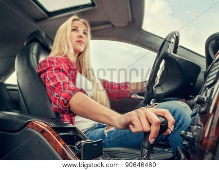 Young attractive blonde girl driving a car with an automatic gear box