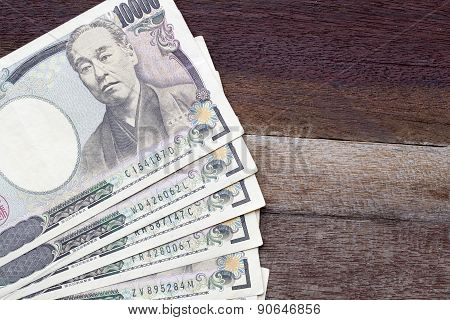 Ten Thousand Yen Banknotes On Wooden Background