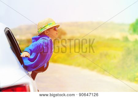 little boy travel by car in summer mountains