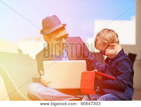 father and son with laptop, touch pad in the city