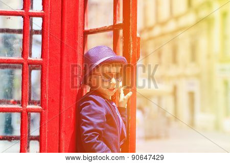 little boy with red telephone box in the city
