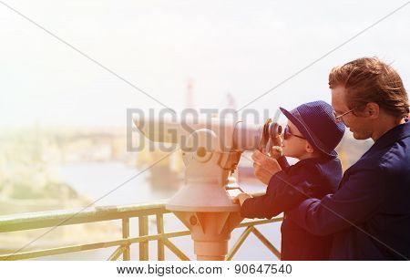 father and son looking through binoculars at the city