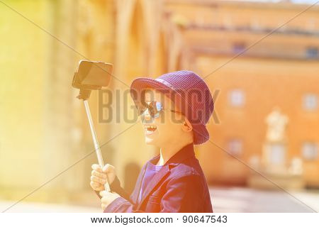 happy little boy taking selfie stick picture while travel in Europe