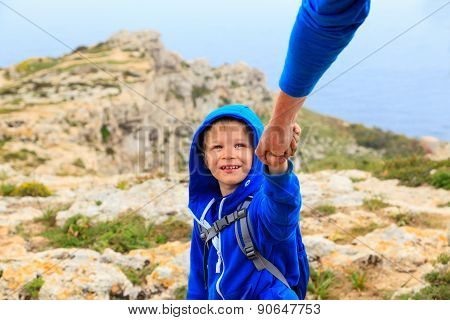 little boy helped by parent on hiking in mountains
