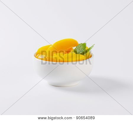 bowl of fruit salad with compote peaches and mint