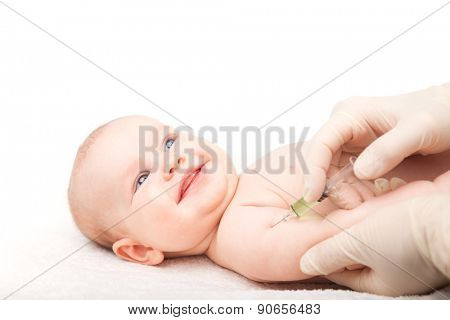 Pediatrician giving a three month baby girl  intramuscular injection in arm. Child looking at a doctor cheerfully