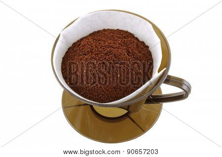 A brown Coffee cone with filter paper full of fresh Ground coffee