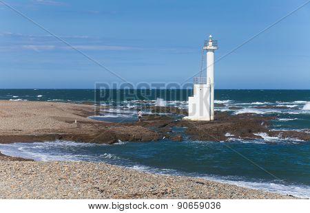 Lighthouse on the beach against blue sky