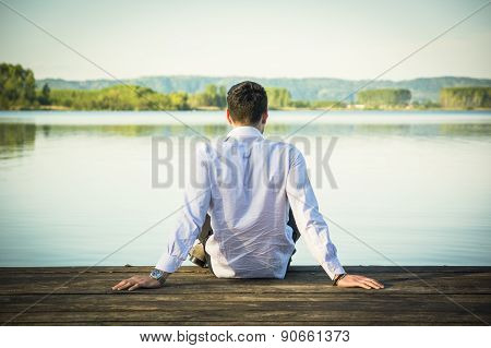 Handsome young man on lake in a sunny, peaceful day