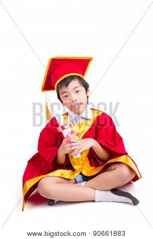 Cute Little Boy Wearing Red Gown Kid Graduation With Mortarboard And Kindergarten Certificate In His