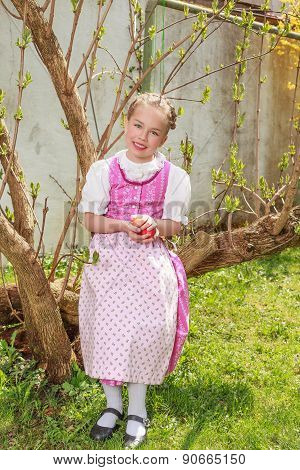 Girls in the dirndl sit in the garden and plays laughing with Easter eggs