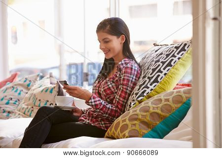 Young woman sitting on sofa in a cafe