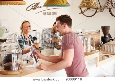 Young men paying for order in a cafe