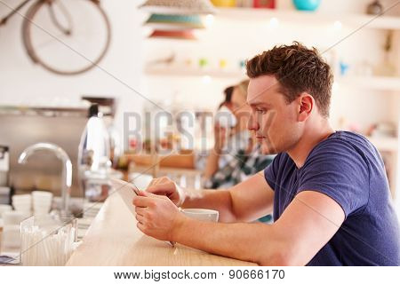 Young man using tablet computer in a cafe