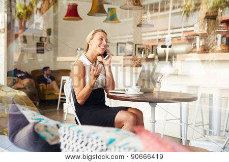 Businesswoman using phone in a coffee shop