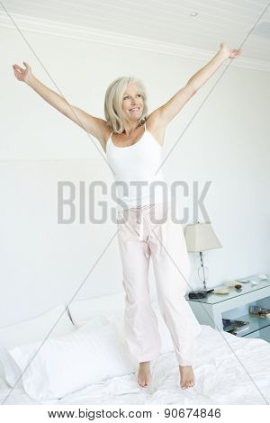 Senior Woman Jumping on Bed