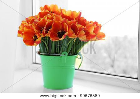 Beautiful bouquet of tulips in metal bucket on windowsill