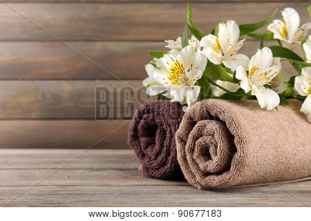 Towels with beautiful flowers on wooden background