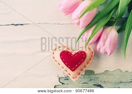 Beautiful pink tulips with decorative heart on wooden background