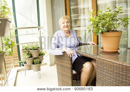 Lady On Balcony With Flowers