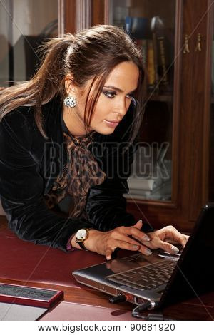 Young happy woman uses laptop computer in office