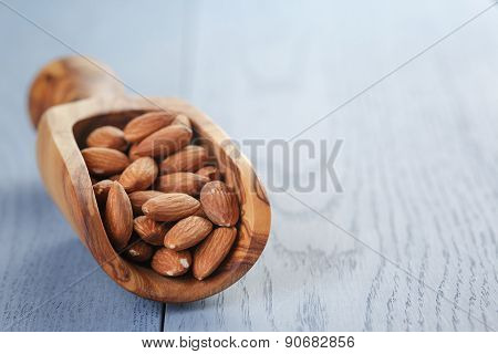 roasted almonds in measuring scoop on blue wooden table