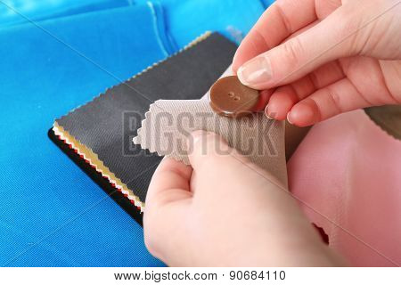 Colorful fabric samples and button in female hands, closeup view