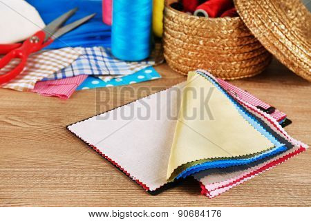 Colorful fabric samples and wicker basket of threads on wooden table background