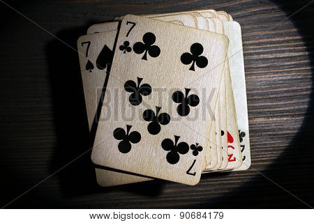 Stack of playing cards in light on wooden table, top view