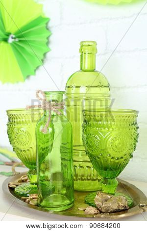 Green glasses and bottles on table on brick wall background