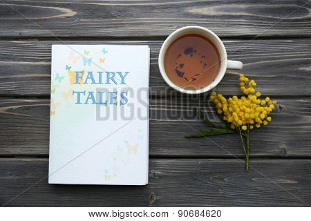 Fairy Tales book with cup of tea and sprig of mimosa on wooden background