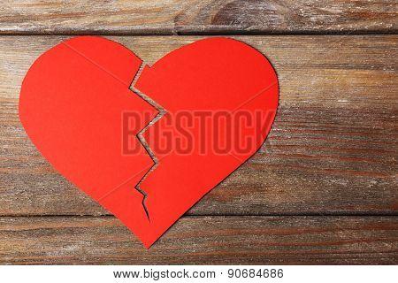 Broken heart on wooden planks background