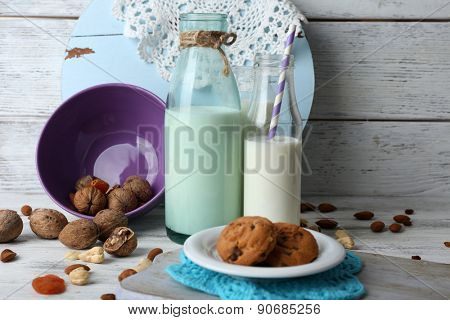 Milk in glassware with walnuts and cookies on background