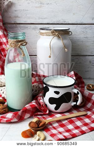 Milk in glassware with walnuts and cookies on wooden table with napkin, closeup