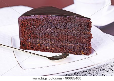 Piece of chocolate cake on white plate, closeup